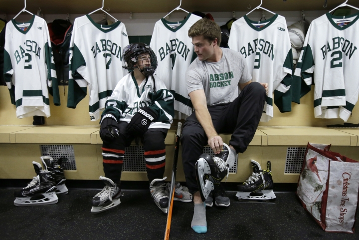 Coleman Walsh, 10, of Walpole, Mass., left, gears up with Babson College men's ice hockey team captain Charlie Ackerman, of Bradenton, Fla., right, following ceremonies held to sign an official letter of intent, Tuesday, Oct. 10, 2017, in Wellesley, Mass., to induct Walsh to the team. Since birth, Coleman has been fighting Williams syndrome, a developmental disorder that affects numerous parts of the body. The induction was organized by Team IMPACT, a national nonprofit that connects colleges with youngsters dealing with debilitating or life-threatening illness. (AP Photo/Steven Senne)