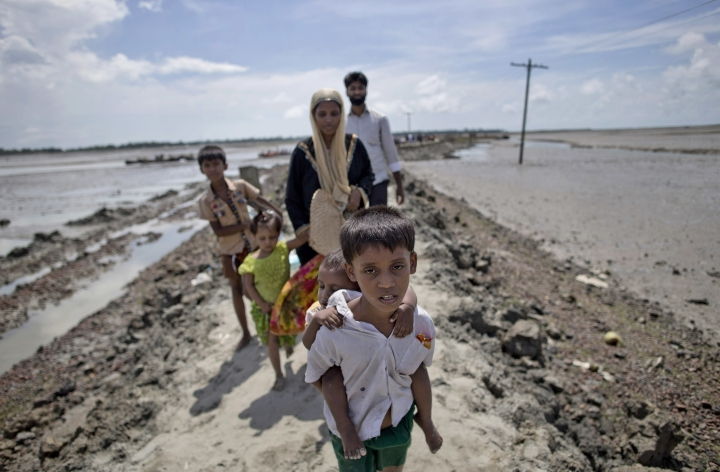 In this Oct. 2, 2017 photo, newly arrived Rohingya refugee Yosar Hossein, 7, carries his baby sister Noyem Fatima and walks followed by his other siblings and mother Firoza Begum on a mud bank leading to a Bangladesh army run processing center where they will be allotted their camp, in Teknaf, Bangladesh. Barefoot and still wearing his school uniform, the 7-year-old is among more than a half million persecuted Rohingya Muslims fleeing neighboring Myanmar. (AP Photo/Gemunu Amarasinghe)