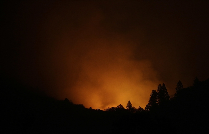 Fire from a distant mountain is seen from Kenwood, Calif., Tuesday, Oct. 10, 2017. Some of the largest blazes in Northern California were in Napa and Sonoma counties, home to dozens of wineries that attract tourists from around the world. (AP Photo/Jeff Chiu)