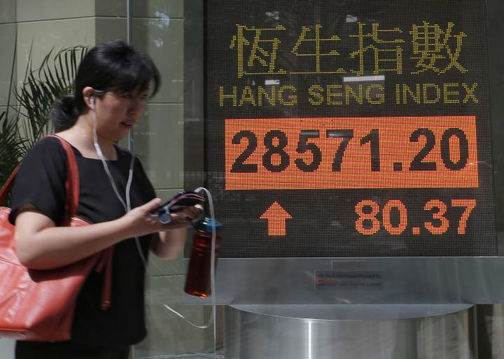 A woman walks past an electronic board showing Hong Kong share index outside a local bank in Hong Kong, Wednesday, Oct. 11, 2017. Asian stocks advanced Wednesday after Wall Street's main index closed at a record high and Spain's Catalonia crisis eased after an independence leader backed away from plans to break away immediately. (AP Photo/Vincent Yu)