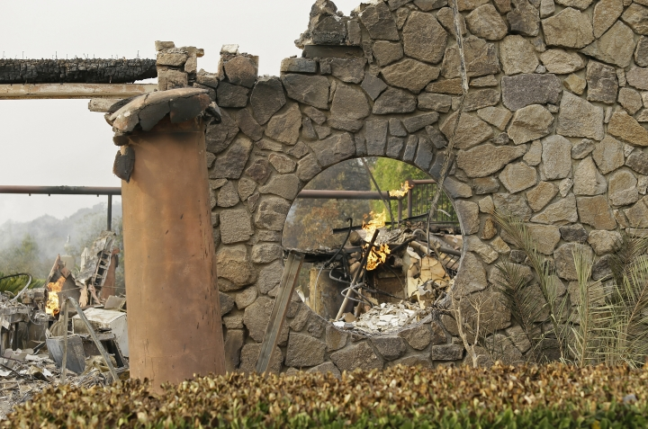 Flames continue to smolder at the Signorello Estate winery Tuesday, Oct. 10, 2017, in Napa, Calif. Worried California vintners surveyed the damage to their vineyards and wineries Tuesday after wildfires swept through several counties whose famous names have become synonymous with fine food and drink. (AP Photo/Eric Risberg)