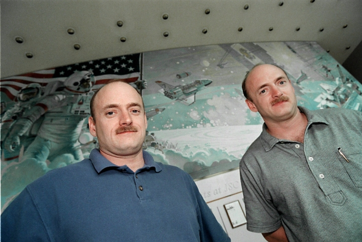 FILE - In this March 25, 1999 file photo, NASA astronauts Scott, left, and Mark Kelly, who are twins, pose for a picture in front of a mural at Johnson Space Center in Houston. In his new autobiography, the retired astronaut Scott Kelly writes about his U.S. record-breaking year in space and the challenging life events that got him there. (AP Photo/Michael Stravato)