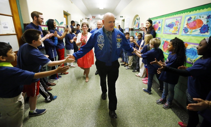 FILE - In this Thursday, May 19, 2016 file photo, retired astronaut Scott Kelly, center, and his twin brother Mark Kelly, back, are greeted by children in the hallway of the Kelly Elementary School after the school was named in their honor in West Orange, N.J. On Wednesday, May 25, 2016, NASA's yearlong spaceman, Scott Kelly, says even after 2 ½ months back on Earth, his feet are still sore. (AP Photo/Julio Cortez)