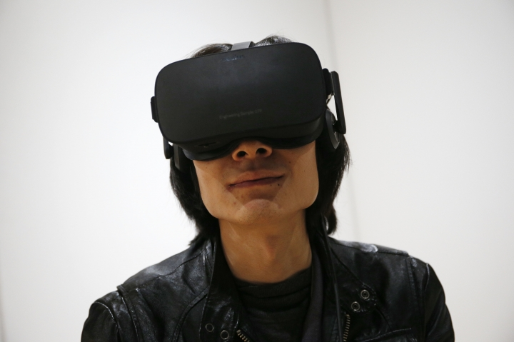 FILE - In this Jan. 6, 2016, file photo, Peijun Guo wears the Oculus Rift VR headset at the Oculus booth at CES International in Las Vegas. Facebook CEO Mark Zuckerberg seems to be realizing a sobering reality about virtual reality: The headsets his company's Oculus division has been making to put users into artificial worlds are too expensive and confining to appeal to the masses. (AP Photo/John Locher, File)