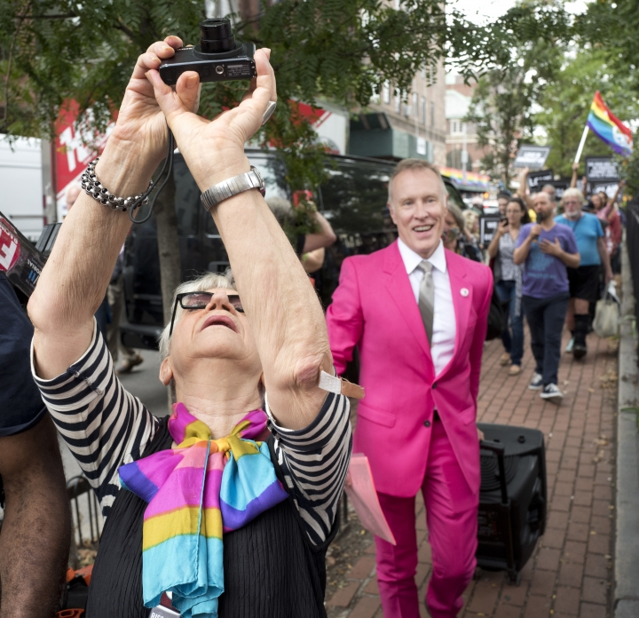 A woman photographs the Rainbow Flag at the Stonewall National Monument, Wednesday, Oct. 11, 2017, in New York. The flag, an international symbol of LGBT liberation and pride, was hoisted on a flagpole for the first time at the monument. (AP Photo/Mark Lennihan)