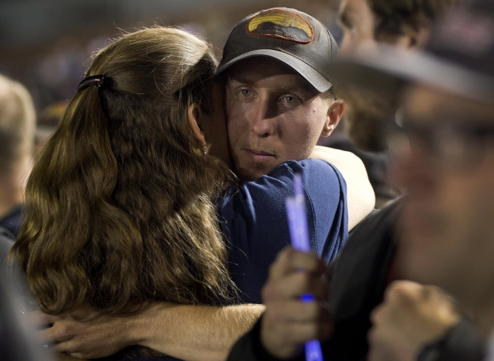 "FILE - In this July 2, 2013, file photo, firefighter Brendan McDonough embraces a mourner near the end of a candlelight vigil in Prescott, Ariz. McDonough, the only member of an Arizona firefighting crew to survive a deadly 2013 wildfire near Yarnell, Ariz., attended the premiere of ""Only The Brave"", the movie that chronicles the wildfire that killed 19 of his fellow firefighters. (AP Photo/Julie Jacobson, File)"