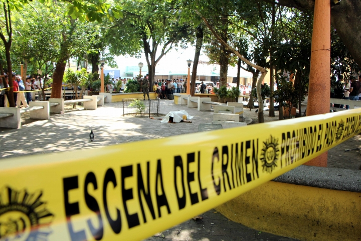 FILE - In this March 10, 2015 file photo, the covered body of journalist Federico Benjamin Salazar Geronimo lies on the ground in the central park of Mazatenango, Guatemala. Gunmen shot and killed two journalists, Salazar and Danilo Efrain Zapon Lopez, and wounded a third as they walked in the park in southern Guatemala. On Oct. 11, 2017 a Guatemalan court sentenced Sergio Valdemar Cardona, who was driving the motorcycle from which they were shot, to 30 years in prison for the murders, while the alleged shooter Eduardo Ariel Mazariegos Ramirez remains fugitive. (AP Photo/Prensa Libre, File)