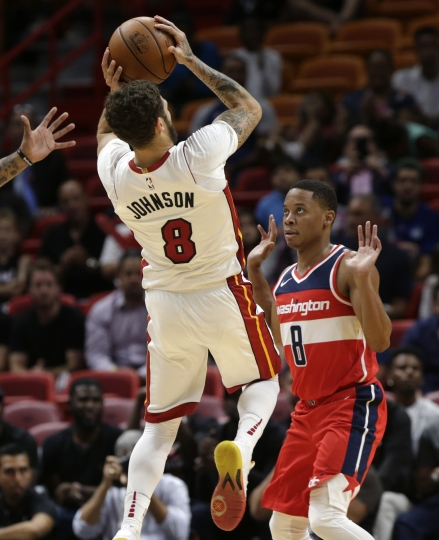 Miami Heat's Tyler Johnson (8) shoots over Washington Wizards' Tim Frazier (8) during the first half of a preseason NBA basketball game, Wednesday, Oct. 11, 2017, in Miami. (AP Photo/Lynne Sladky)