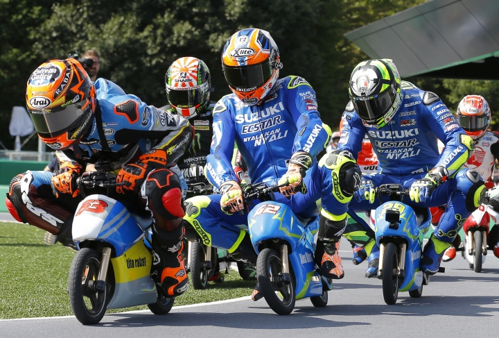MotoGP rider Tito Rabat, right, of Spain steers his mini electric motorcycle as he leads the pack of riders during a fan event at the Twin Ring Motegi circuit ahead of the MotoGP Japanese Motorcycle Grand Prix in Motegi, north of Tokyo, Thursday, Oct. 12, 2017. (AP Photo/Shizuo Kambayashi)