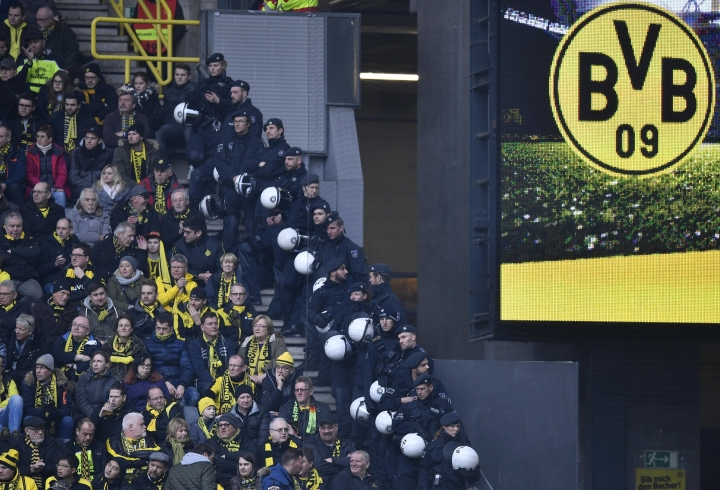 FILE - In this Feb. 18, 2017 file photo police wait behind Dortmund supporters during the German Bundesliga soccer match between Borussia Dortmund and VfL Wolfsburg in Dortmund. Police are braced for trouble on Saturday Oct. 14, 2017 as Leipzig returns to Borussia Dortmund in the Bundesliga for the first time since violent scenes overshadowed their game last season. Dortmund was fined and forced to close its 24,454-capacity south stand for one game following Leipzig's previous visit on Feb. 4, when some of its fans were attacked with stones and bottles, police officers were injured. (AP Photo/Martin Meissner,file)