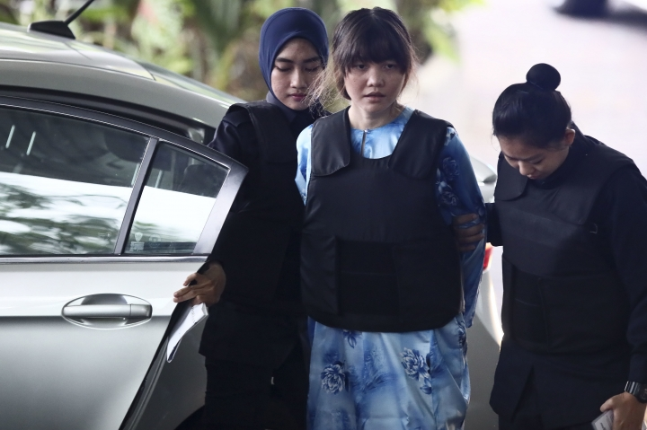 Vietnamese Doan Thi Huong, center, is escorted by police officers as she arrives for a court hearing at Shah Alam court house in Shah Alam, outside Kuala Lumpur, Malaysia, Thursday, Oct. 12, 2017. Security camera videos showed Wednesday Kim Jong Nam, the estranged half brother of North Korea's leader, being attacked at a Malaysian airport and the two suspects, including Doan, hurrying away afterward have been presented at their murder trial. (AP Photo/Sadiq Asyraf)