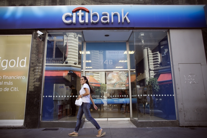FILE - In this Tuesday, March 17, 2015, file photo, a woman walks by a Citibank branch in Buenos Aires, Argentina. Citigroup Inc. reports earnings Thursday, Oct. 12, 2017. (AP Photo/Victor R. Caivano, File)