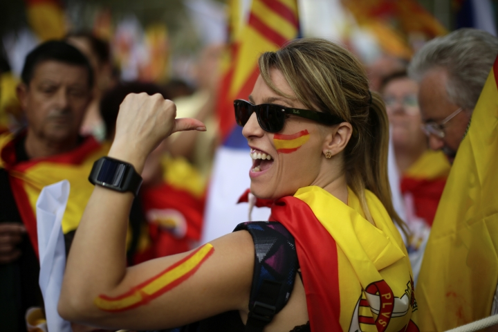 """A woman wearing the Spanish colors gestures as she joins others celebrating a holiday known as """"Dia de la Hispanidad"""" or Spain's National Day in Barcelona, Spain, Thursday, Oct. 12, 2017. Spain's celebrates its national day amid one of the country's biggest crises ever as its powerful northeastern region of Catalonia threatens independence. (AP Photo/Manu Fernandez)"""