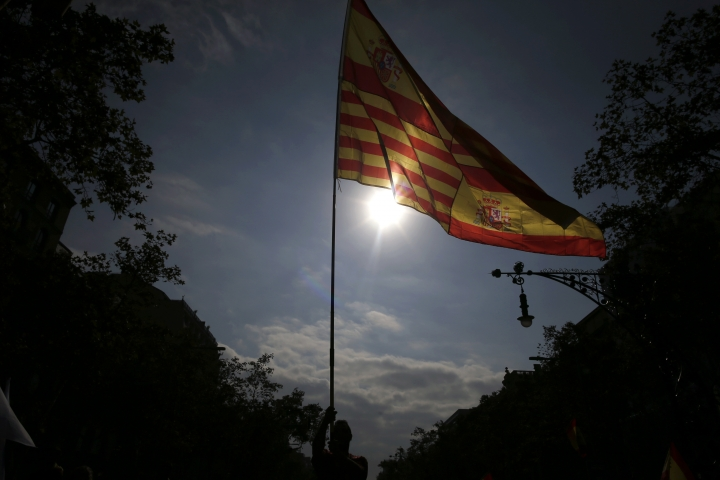 """A person holds a pole with the flags of Catalonia and Spain as people celebrate a holiday known as """"Dia de la Hispanidad"""" or Spain's National Day in Barcelona, Spain, Thursday, Oct. 12, 2017. Spain's celebrates its national day amid one of the country's biggest crises ever as its powerful northeastern region of Catalonia threatens independence. (AP Photo/Manu Fernandez)"""