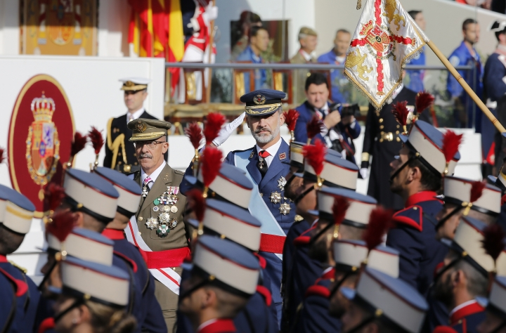 """Spain's King Felipe, center, salutes as troops march past during a parade to mark the national holiday known as """"Dia de la Hispanidad"""" or Hispanic Day, in Madrid, Spain, Thursday, Oct. 12, 2017. King Felipe VI is to preside over the annual colorful parade Thursday as Spain awaits a response to a government request to Catalonia to clarify by Monday if it has already declared independence, in which case Spain warns it may begin taking control of the region. (AP Photo/Paul White)"""