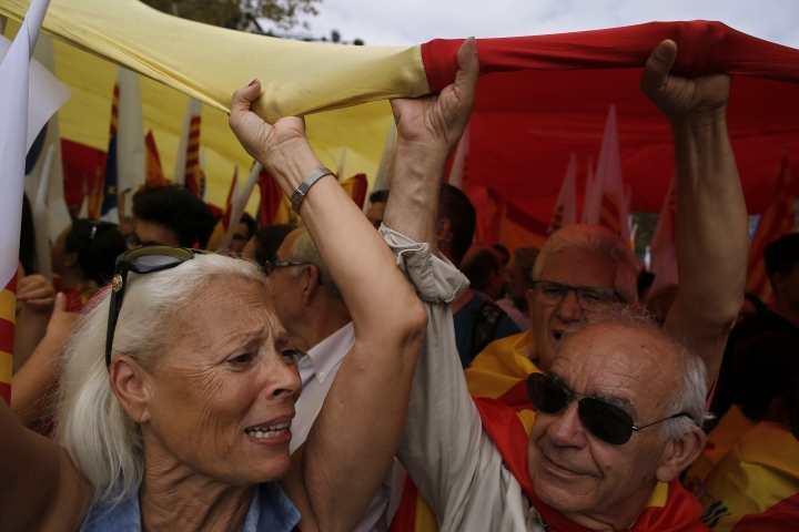 "People carry a Spanish flag above their heads as they celebrate a holiday known as ""Dia de la Hispanidad"" or Spain's National Day in Barcelona, Spain, Thursday, Oct. 12, 2017. Spain's celebrates its national day amid one of the country's biggest crises ever as its powerful northeastern region of Catalonia threatens independence. (AP Photo/Manu Fernandez)"