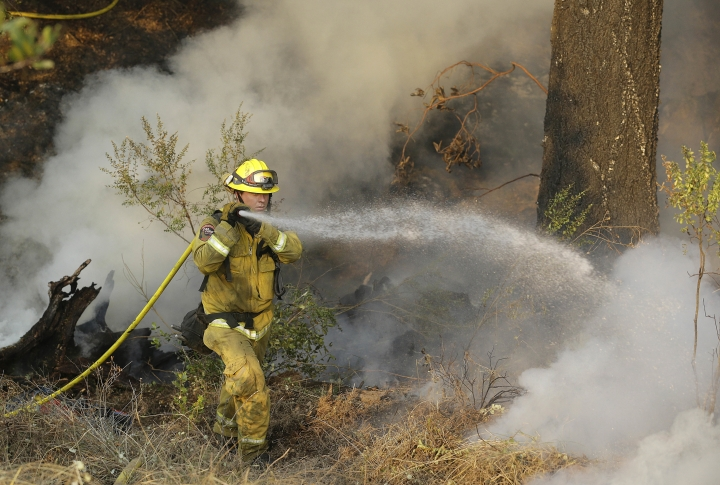 A Cal Fire firefighter works on hot spots on a hill in the Oakmont area of Santa Rosa, Calif., Thursday, Oct. 12, 2017. A forecast for gusty winds and dry air threatened to fan the fires, which are fast becoming the deadliest and most destructive in California history after destroying thousands of homes and businesses. . (AP Photo/Jeff Chiu)