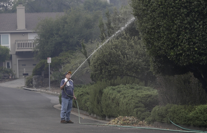 FILE - In this Oct 10, 2017, file photo, Leonard George sprays down trees in front of his house in the Oakmont area of Santa Rosa, Calif. For many residents in the path of one of California's deadliest blazes, talk is of wind direction, evacuations and goodbyes. (AP Photo/Jeff Chiu, File)