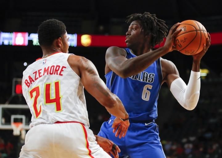 Dallas Mavericks forward Johnathan Motley (6) looks to pass around Atlanta Hawks forward Kent Bazemore (24) in the second half of an NBA preseason basketball game on Thursday, Oct. 12, 2017, in Atlanta. (AP Photo/Todd Kirkland)