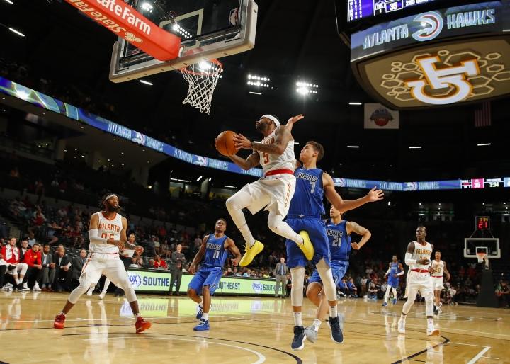 Atlanta Hawks guard Malcolm Delaney (5) goes up to shoot as Dallas Mavericks guard Dennis Smith Jr. (1) defends in the first half of an NBA preseason basketball game Thursday, Oct. 12, 2017, in Atlanta. (AP Photo/Todd Kirkland)