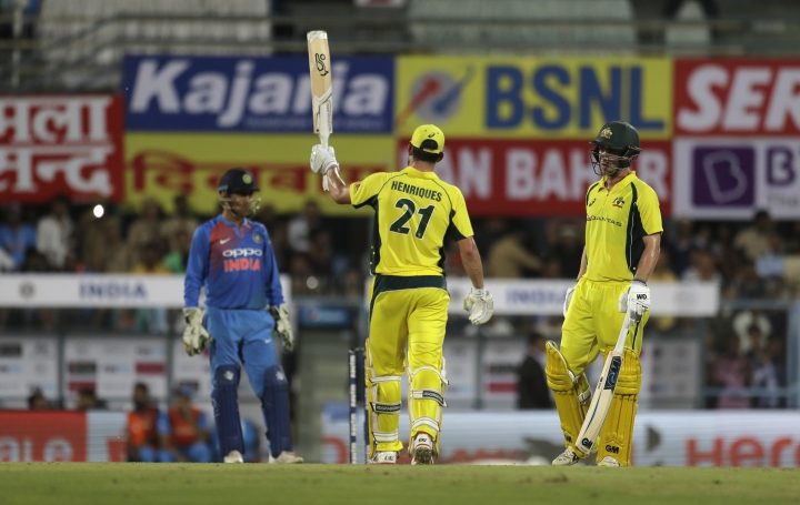Australia's Moises Henriques, center, raises his bat after scoring fifty runs as his teammate Travis Head looks on during second Twenty20 cricket match against India in Gauhati, India, Tuesday, Oct. 10, 2017. (AP Photo/Manish Swarup)