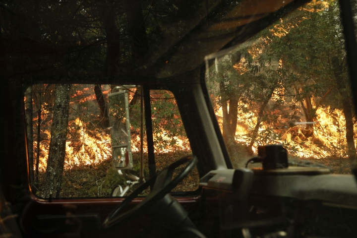 A wildfire burning along the Highway 29 is seen through a fire truck Thursday, Oct. 12, 2017, near Calistoga, Calif. More than 8,000 firefighters are battling the blazes and additional manpower and equipment was pouring in from across the country and as far as Australia and Canada. (AP Photo/Jae C. Hong)