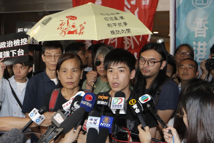 Former student leader Lester Shum, center, one of the activists found guilty of contempt of court, speaks to media at the High Court in Hong Kong, Friday, Oct. 13, 2017. The court has convicted 20 activists, including Shum and leader Joshua Wong, for defying authorities trying to clear a protest site during massive 2014 pro-democracy demonstrations in the Chinese-controlled city. (AP Photo/Kin Cheung)