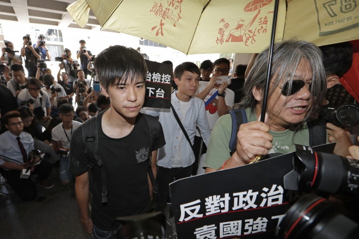 """Former student leader Lester Shum, left, arrives at the High Court to hear the verdict in a case of contempt against him and other activists in Hong Kong, Friday, Oct. 13, 2017. The court has convicted 20 activists, including Shum and leader Joshua Wong, for defying authorities trying to clear a protest site during massive 2014 pro-democracy demonstrations in the Chinese-controlled city. The Chinese words on placard read """"Against political prosecution, Rimsky Yuen Kwok-keung step down."""" (AP Photo/Kin Cheung)"""