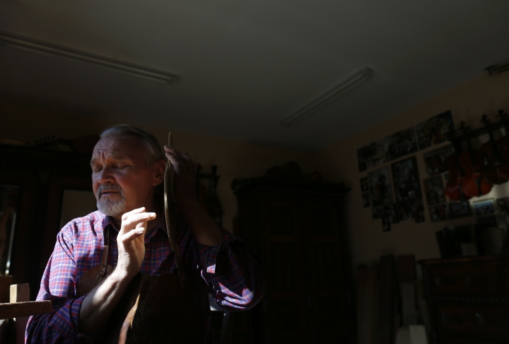 Violin maker Jan Nemcek knocks on the future violin body to hear the sound, in the northern Serbian village of Kovacica, Wednesday, Oct. 4, 2017. Nemcek picks up his own wood from the forest, cuts and dries it himself and then slowly and patiently moulds it into a musical instrument. Nemcek is a violin maker a rare one that makes violins the old way _ using no machines, but only his hands and tools. (AP Photo/Darko Vojinovic)