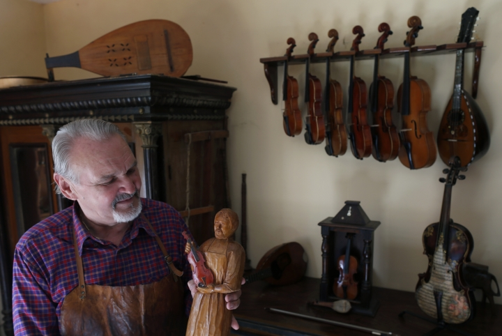 Violin maker Jan Nemcek shows a wooden statue of him, made by his wife, in the northern Serbian village of Kovacica, Wednesday, Oct. 4, 2017. Nemcek is a violin maker a rare one that makes violins the old way _ using no machines, but only his hands and tools. (AP Photo/Darko Vojinovic)