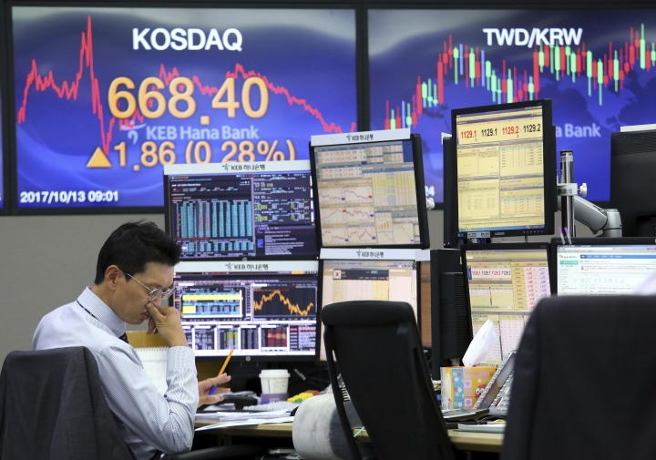 A currency trader watches documents at the foreign exchange dealing room of the KEB Hana Bank headquarters in Seoul, South Korea, Friday, Oct. 13, 2017. Asian stock markets were subdued on Friday following losses on Wall Street as investors awaited corporate earnings and U.S. inflation data.(AP Photo/Ahn Young-joon)