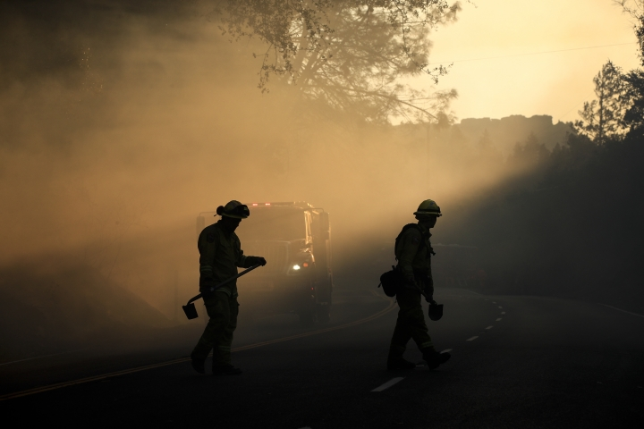 Two firefighters watch for spot fires Friday, Oct. 13, 2017, near Calistoga, Calif. Firefighters gained some ground on a blaze burning in the heart of California's wine country but face another tough day ahead with low humidity and high winds expected to return. (AP Photo/Jae C. Hong)
