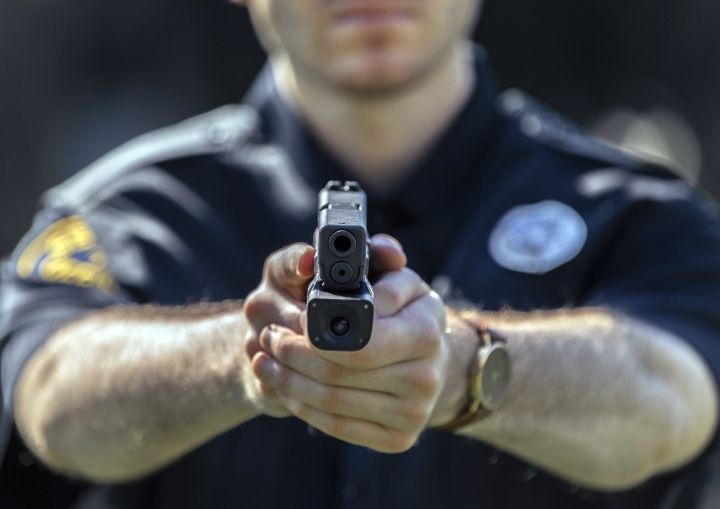 In this Aug. 14 2017 photo provided by Centinel Solutions, a model displays a camera mounted below the barrel of a handgun in West Palm Beach, Fla. Some police departments are considering putting cameras on officers' guns, saying they would give a better, unobstructed view of police-involved shootings and save money on video storage costs compared with body cameras. (Gavin Smith/Centinel Solutions via AP)