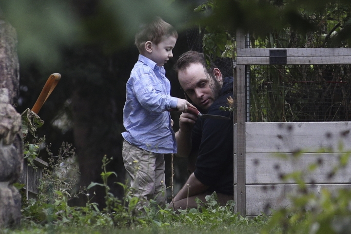 ADDS NAME OF SON JONAH- Joshua Boyle and son Jonah play in the garden at his parents house in Smiths Falls, Ont., on Saturday, Oct. 14, 2017. A couple held hostage for five years by a Taliban-linked network and forced to raise three children while in captivity were initially targeted for ransom because of the impending birth of their first child, the Canadian man at the heart of the case speculated Saturday. Boyle said he and his wife Caitlan Coleman heard at least half a dozen reasons why they had been snatched from a village in Afghanistan and held against their will by the Haqqani network over the years they were imprisoned. (Lars Hagberg/The Canadian Press via AP)