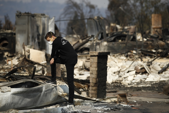 """Benjamin Lasker, 16, pauses while looking at what remains of his home after a wildfire swept through Sunday, Oct. 15, 2017, in Santa Rosa, Calif. With the winds dying down, fire officials said Sunday they have apparently """"turned a corner"""" against the wildfires that have devastated California wine country and other parts of the state over the past week, and thousands of people got the all-clear to return home. (AP Photo/Jae C. Hong)"""