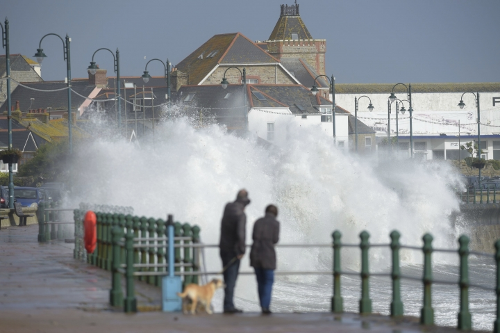 A couple watch waves break on the sea wall at Penzanze, southwestern England as the remnants of Hurricane Ophelia begins to hit parts of Britain and Ireland. Ireland's meteorological service is predicting wind gusts of 120 kph to 150 kph (75 mph to 93 mph), sparking fears of travel chaos. Some flights have been cancelled, and aviation officials are warning travelers to check the latest information before going to the airport Monday. (Ben Birchall/PA via AP)