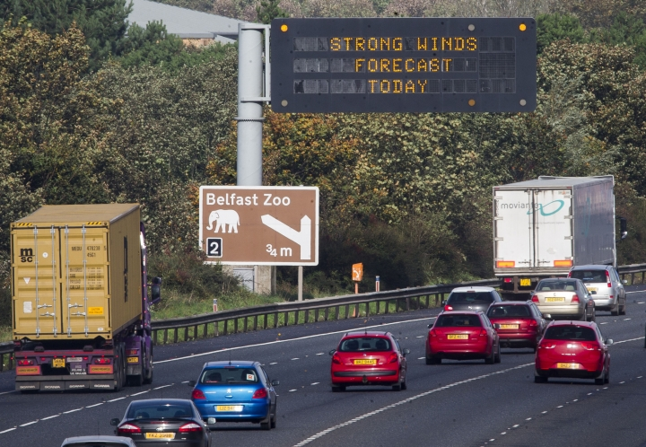 """An overhead road sign on the M2 motorway near Belfast, Northern Ireland warns drivers of, """"Strong Winds Forecast Today"""", as the remnants of Hurricane Ophelia begins to hit Ireland and parts of Britain. Ireland's meteorological service is predicting wind gusts of 120 kph to 150 kph (75 mph to 93 mph), sparking fears of travel chaos. Some flights have been cancelled, and aviation officials are warning travelers to check the latest information before going to the airport Monday. (Liam McBurney/PA via AP)"""