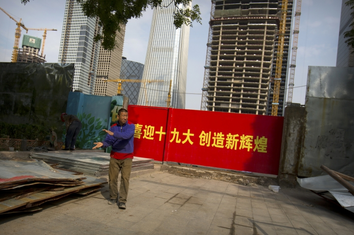 """In this Thursday, Oct. 12, 2017, photo, a worker walks past a billboard stating """"Welcome the 19th Party Congress, create new glories"""" outside of a construction site in Beijing. As China's ruling Communist Party kicks off its twice-a-decade national congress on Wednesday, buildings, bridges and construction sites around Beijing have been festooned with banners heralding the party's merits and its goal of realizing the """"Chinese Dream"""" of greater prosperity. (AP Photo/Mark Schiefelbein)"""