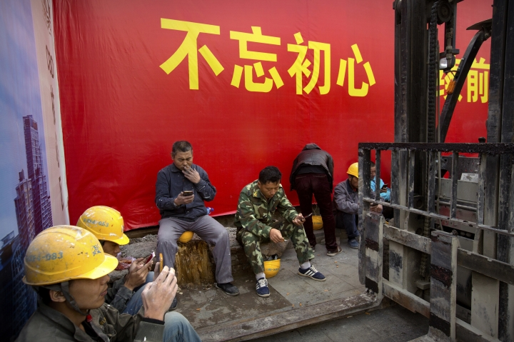 """In this Thursday, Oct. 12, 2017, photo, construction workers rest near a billboard stating """"Don't forget why we started, continue to move forward"""" in Beijing. As China's ruling Communist Party kicks off its twice-a-decade national congress on Wednesday, buildings, bridges and construction sites around Beijing have been festooned with banners heralding the party's merits and its goal of realizing the """"Chinese Dream"""" of greater prosperity. (AP Photo/Mark Schiefelbein)"""