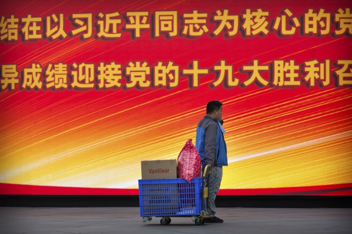 "In this Friday, Oct. 13, 2017 photo, a deliveryman pauses near an electronic display board showing a slogan for the upcoming Communist Party congress in Beijing. As China's ruling Communist Party kicks off its twice-a-decade national congress on Wednesday, buildings, bridges and construction sites around Beijing have been festooned with banners heralding the party's merits and its goal of realizing the ""Chinese Dream"" of greater prosperity. The slogan says ""To more closely unite around the party central committee with Comrade Xi Jinping as the core, welcome the victorious opening of the 19th party congress with excellent achievements."" (AP Photo/Mark Schiefelbein)"