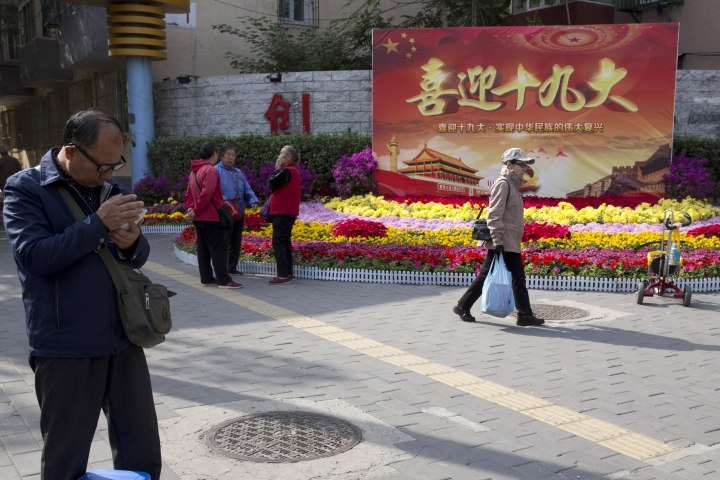 """In this Oct. 16, 2017 photo, residents pass by a board with the words """"Welcome the 19th Congress"""" on the streets of Beijing, China. Extraordinary security measures are being imposed ahead of the party congress, in addition to the typical security forces, thousands of deputized citizens patrol the streets, and knife, fireworks and chemical sales have been suspended. (AP Photo/Ng Han Guan)"""
