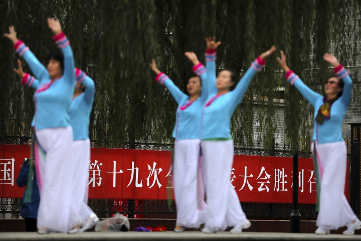 """In this Saturday, Oct. 14, 2017, photo, women from a neighborhood dance group practice near a banner for the upcoming Communist Party congress in Beijing. As China's ruling Communist Party kicks off its twice-a-decade national congress on Wednesday, buildings, bridges and construction sites around Beijing have been festooned with banners heralding the party's merits and its goal of realizing the """"Chinese Dream"""" of greater prosperity. The banner reads """"Welcome the victorious opening of the 19th Party Congress with excellent achievements."""" (AP Photo/Mark Schiefelbein)"""