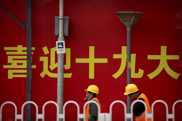 """In this Oct. 12, 2017 photo, construction workers pass by a billboard reading """"Welcome the 19th Party Congress"""" at a construction site in Beijing. Having bested his rivals, Chinese President Xi Jinping is primed to consolidate his already considerable power as the country's ruling Communist Party begins its twice-a-decade national congress on Wednesday, Oct. 18. (AP Photo/Mark Schiefelbein)"""