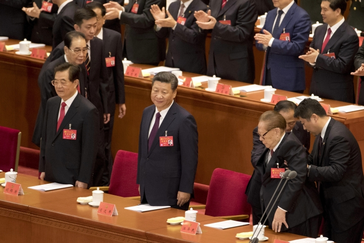 Chinese President Xi Jinping, center, stands with former Chinese President Hu Jintao, left, as former Chinese President Jiang Zemin is assisted into his seat at the opening ceremony of the 19th Party Congress held at the Great Hall of the People in Beijing, China, Wednesday, Oct. 18, 2017. Having bested his rivals, Chinese President Xi Jinping is primed to consolidate his already considerable power as the ruling Communist Party begins its twice-a-decade national congress on Wednesday.(AP Photo/Ng Han Guan)
