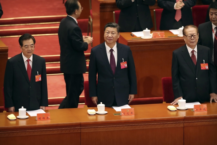 Chinese President Xi Jinping, center, and former Presidents Hu Jintao, left, and Jiang Zemin, right, stand at the beginning of the opening session of China's 19th Party Congress at the Great Hall of the People in Beijing, Wednesday, Oct. 18, 2017. (AP Photo/Mark Schiefelbein)