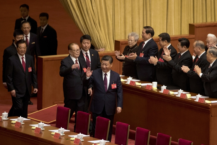 Chinese President Xi Jinping, front right, waves as he walks ahead of former Chinese Presidents Jiang Zemin and Hu Jintao, left, front, as they arrive for the opening ceremony of the 19th Party Congress held at the Great Hall of the People in Beijing, China, Wednesday, Oct. 18, 2017. Having bested his rivals, Xi is primed to consolidate his already considerable power as the ruling Communist Party begins its twice-a-decade national congress on Wednesday.(AP Photo/Ng Han Guan)