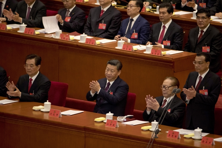 Chinese President Xi Jinping, center, former Chinese President Hu Jintao, left, and former Chinese President Jiang Zemin, second right, applaud near Chinese Premier Li Keqiang, right, during the opening ceremony of the 19th Party Congress held at the Great Hall of the People in Beijing, China, Wednesday, Oct. 18, 2017. Xi has told a key Communist Party congress that the nation's prospects are bright but the challenges are severe. (AP Photo/Ng Han Guan)