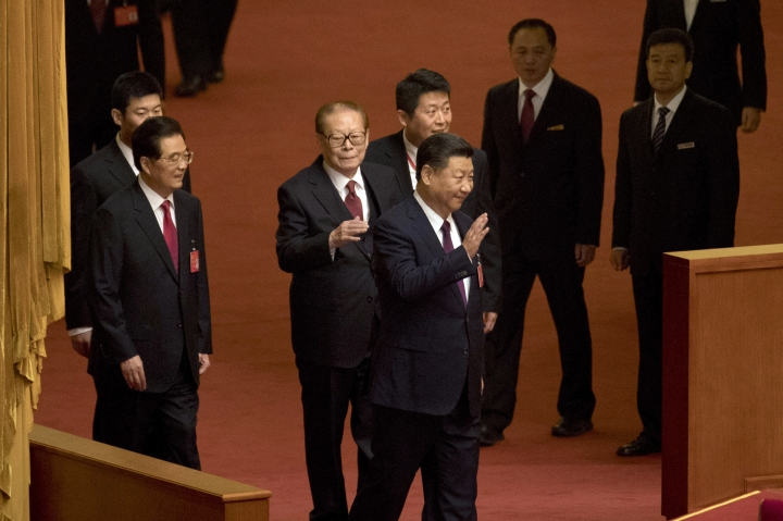 Chinese President Xi Jinping, center, waves as he walks ahead of former Chinese Presidents Jiang Zemin, rear center, and Hu Jintao, front left, as they arrive for the opening ceremony of the 19th Party Congress held at the Great Hall of the People in Beijing, China, Wednesday, Oct. 18, 2017. Having bested his rivals, Xi is primed to consolidate his already considerable power as the ruling Communist Party begins its twice-a-decade national congress on Wednesday.(AP Photo/Ng Han Guan)