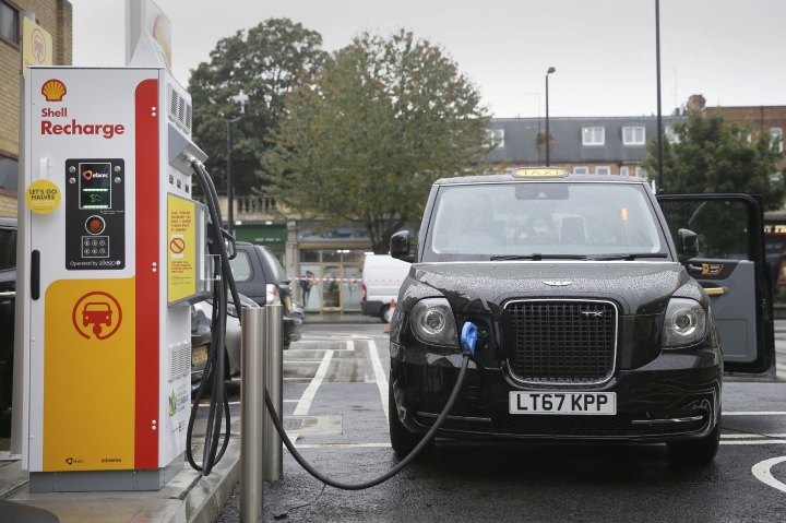 A new TX Cab London taxi is plugged into a charging station during a media opportunity at a Shell petrol station on Holloway road, in London, Wednesday Oct. 18, 2017, 2017. Only days after Shell agreed to buy electric vehicle charging firm NewMotion, Shell are opening three charging stations Wednesday with more expected by the end of the year. (AP Photo/Tim Ireland)