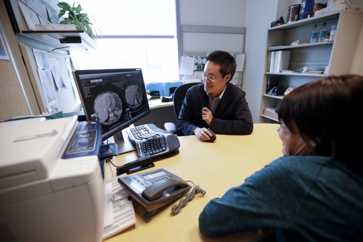 """Patient Alison Cairnes, foreground, looks at images with her doctor Shumei Kato at the University of California San Diego in San Diego on Aug. 15, 2017. Cairnes' cancer was between her stomach and esophagus, and had spread to her liver, lungs and lymph nodes. Tissue testing found 10 abnormal genes, but on the liquid biopsy """"only EGFR popped out"""" as a good target. Two drugs aim at that gene but aren't approved for her type of cancer. A tumor board advised trying the combo. Within two weeks, she quit using pain medicines. After two months, her liver tumor had shrunk roughly by half. (AP Photo/Gregory Bull)"""